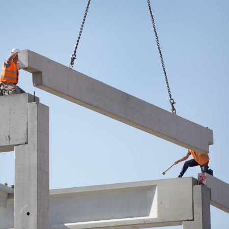 Construction workers standing on concrete beam on height and placing truss lifted by crane